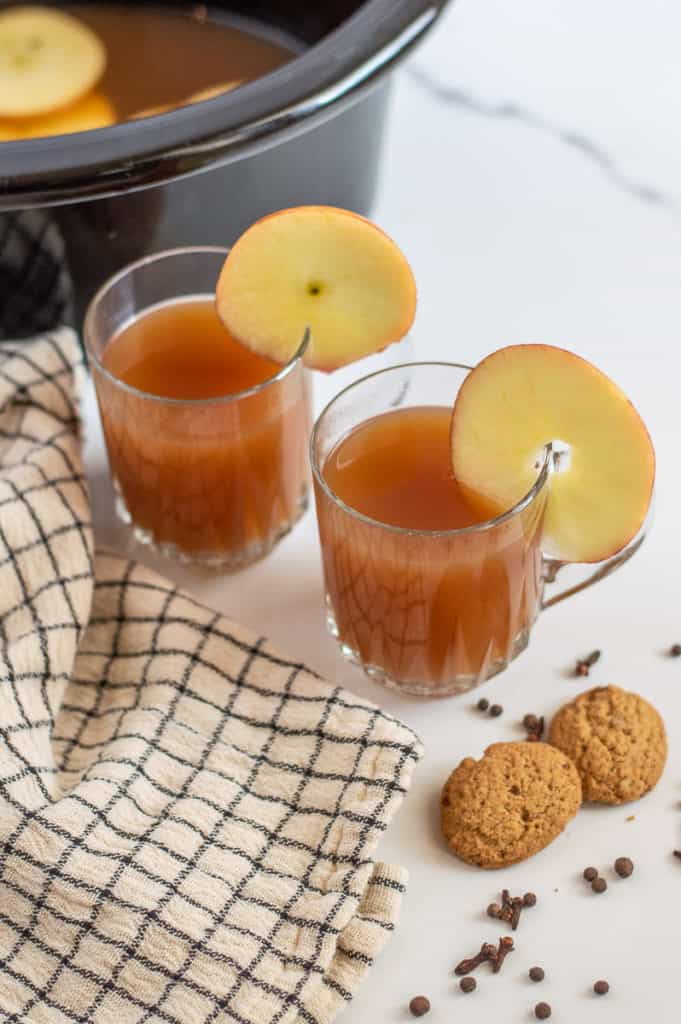 Crockpot apple cider in glass cups with apple slices