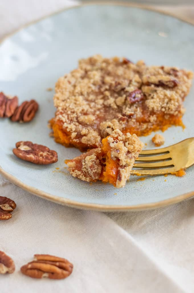 Pecans and sweet potato casserole on a plate with gold fork