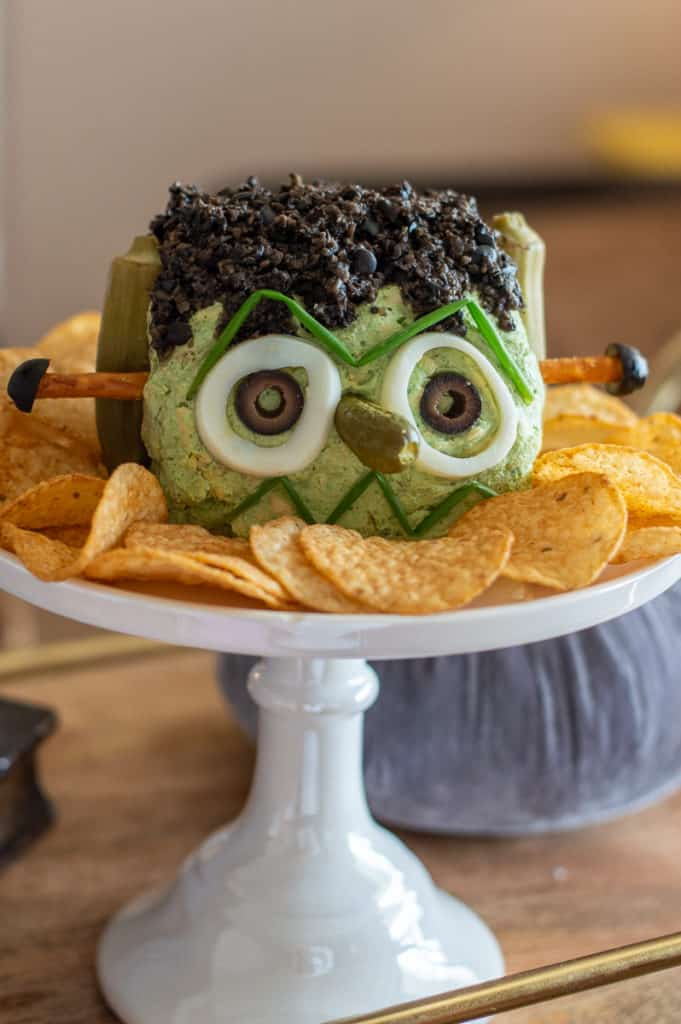 Frankenstein cheese ball with chips on a cake stand