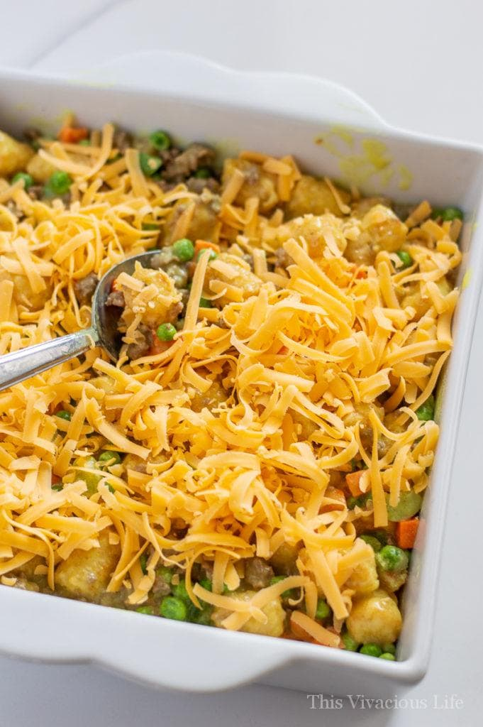 Tater tot casserole being stirred with a spoon and cheese on top