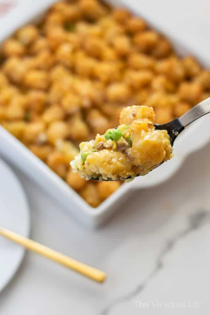 Tater tot casserole on a spoon with main dish behind it
