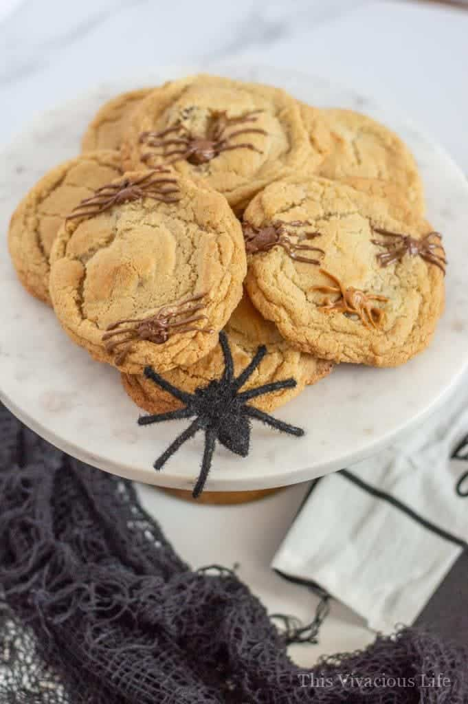 Spider cookies on a marble platter with a black toy spider