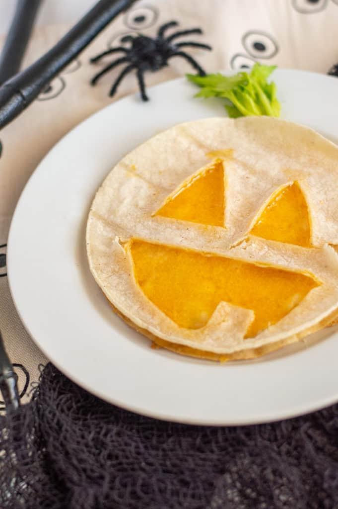 Jack o' lantern quesadilla on a white plate