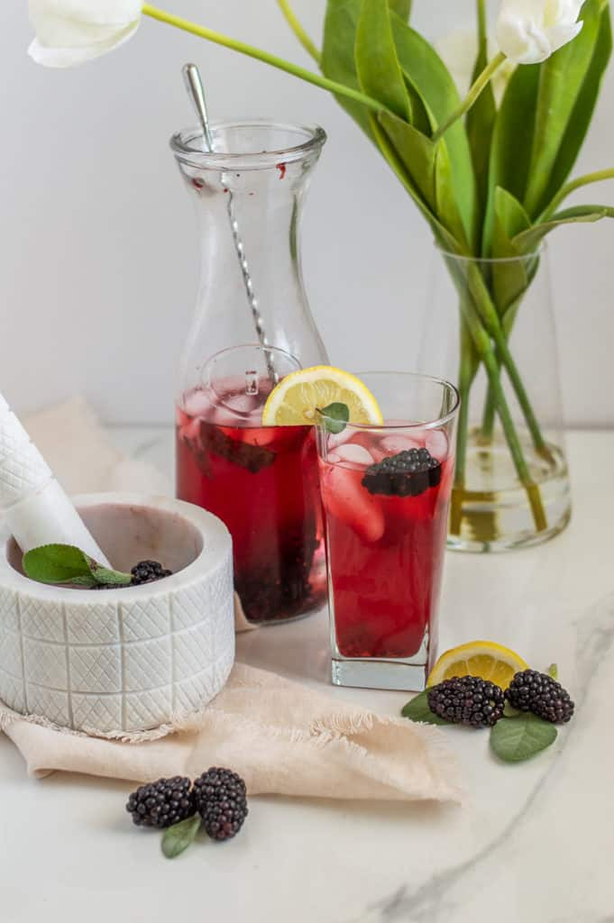 Glass and pitcher with blackberry lemonade near a tea towel