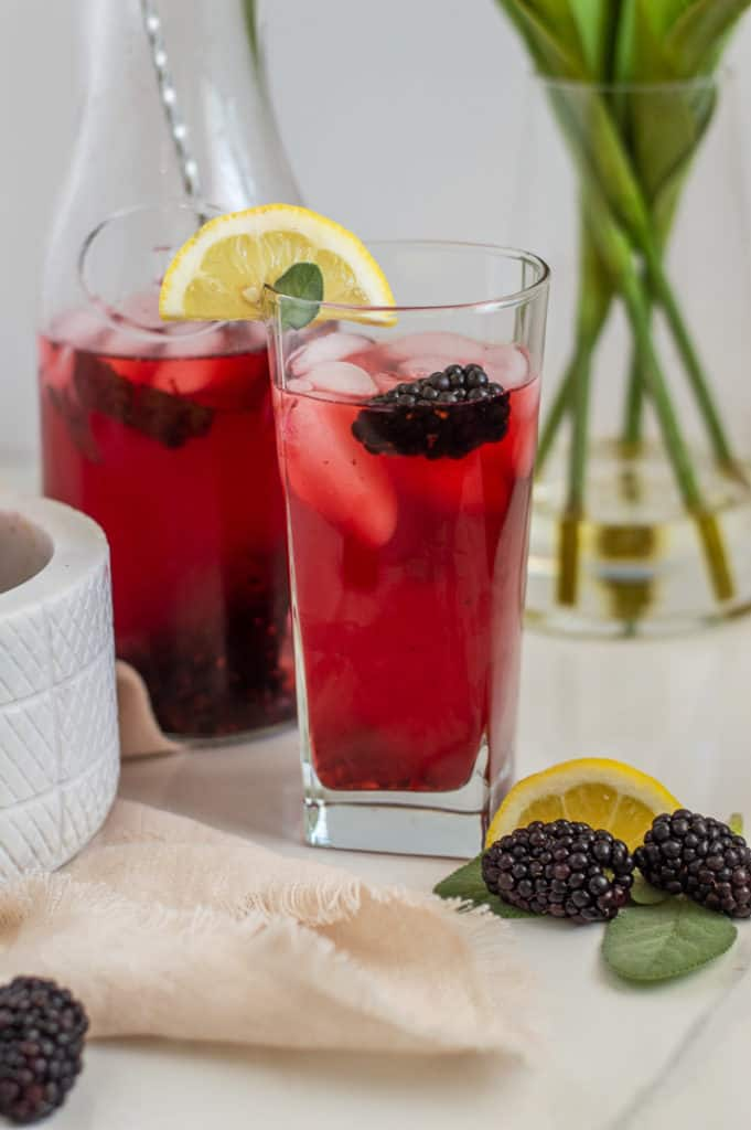 Blackberry lemonade in a glass cup with lemon