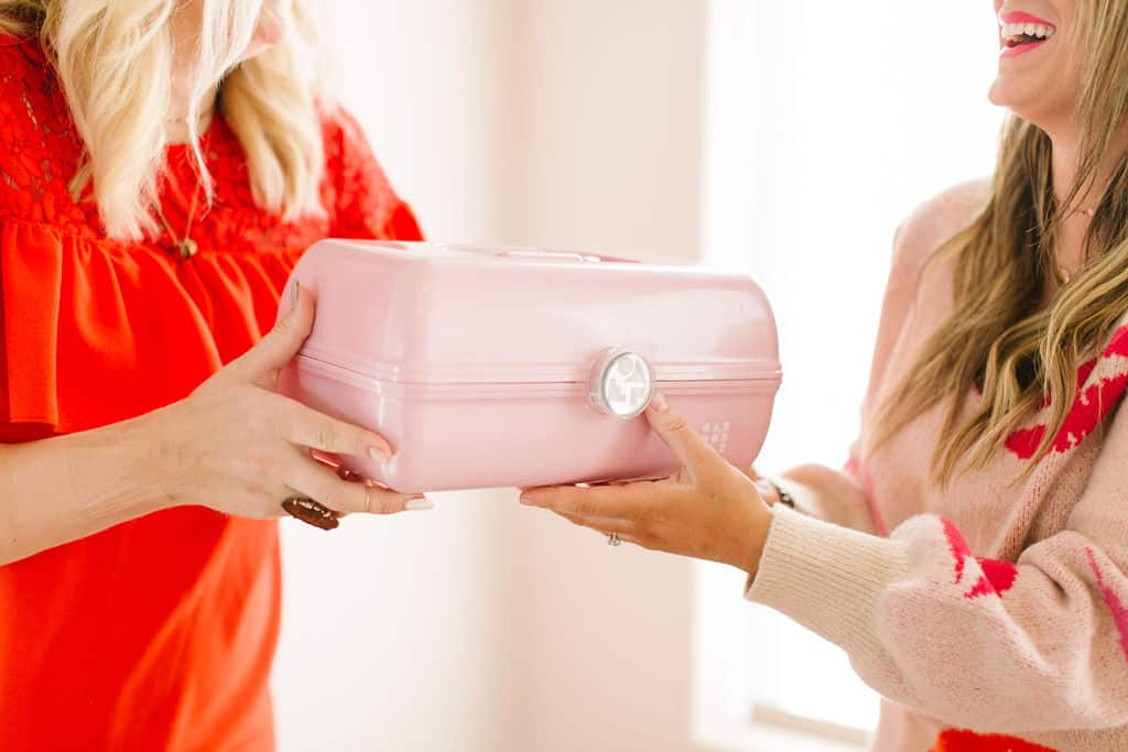 Pink caboodle being handed to a friend