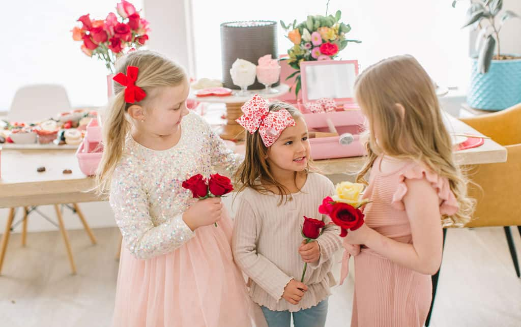 Three little valentines girls with flowers