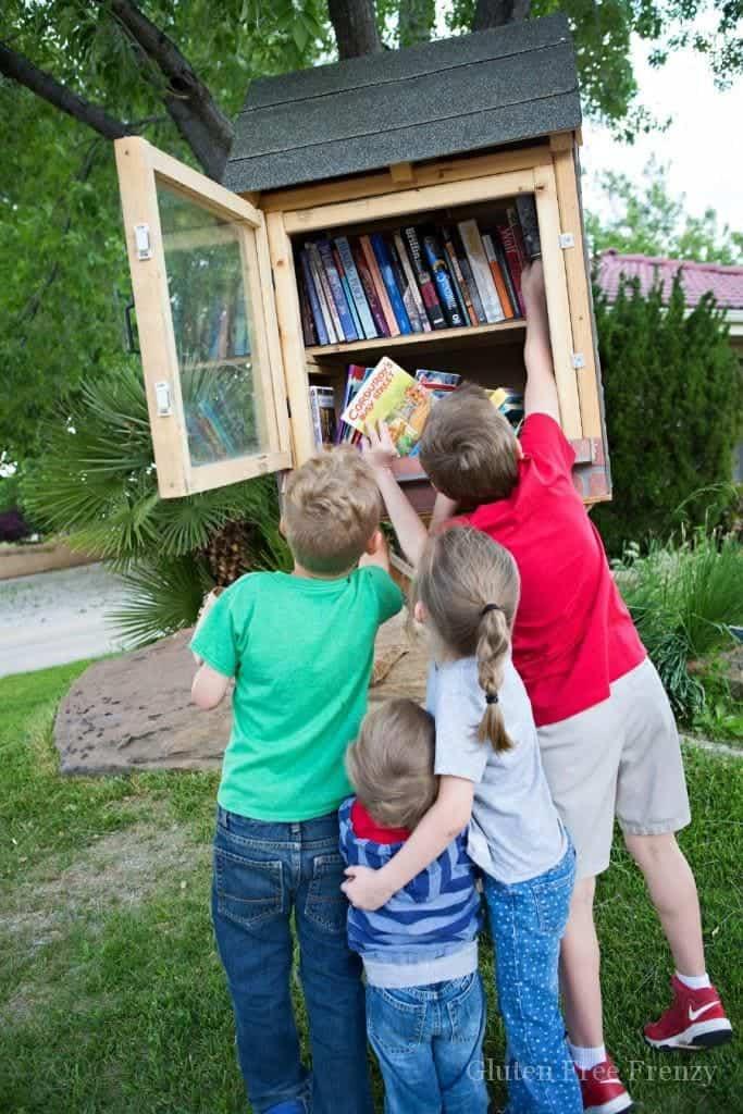 Kids getting books from a little lending library