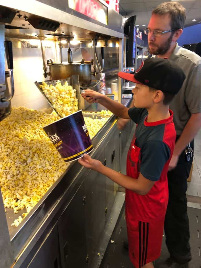 Kid putting popcorn in a bucket