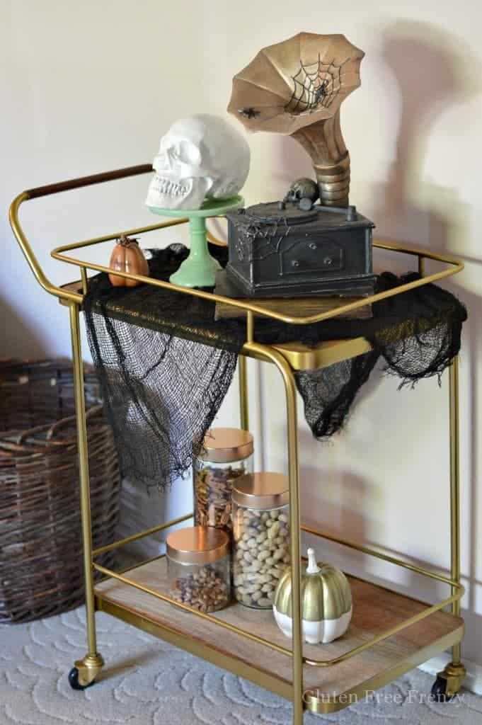 Experience the mysterious magic of the season with a Halloween styled bar cart and treat cart. Decor that can last all month long is easy to achieve without breaking the bank. Add a few spooky touches along with a display of your favorite treats and you will have a fantastic Halloween treat cart perfect for your next party! | Halloween Decorations | How to Decorate for Halloween || This Vivacious Life #halloween #halloweenparty #halloweendecorations #halloweendecor #barcart #thisvivaciouslife