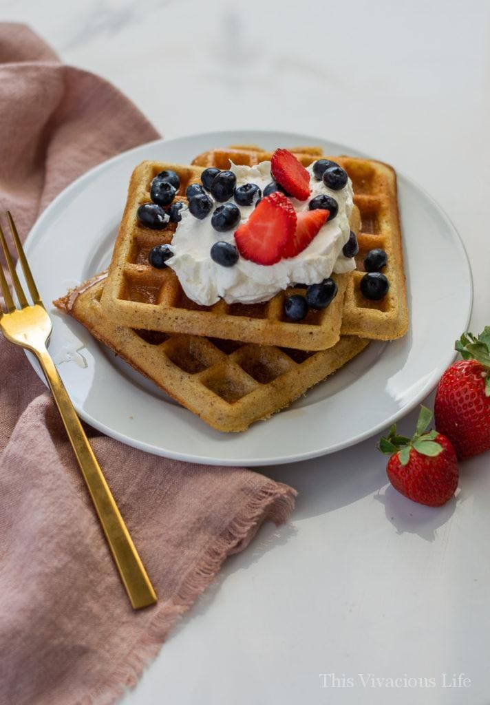 Three waffles on a white plate with gold fork