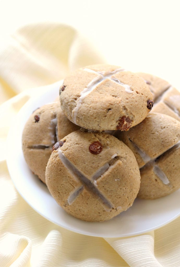 Five hot cross buns on a white plate