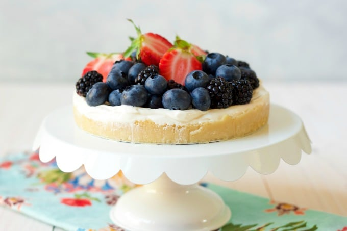 A cheesecake with berries on a white cake stand