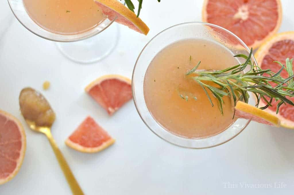 This rosemary and grapefruit honey mocktail is in a martini glass