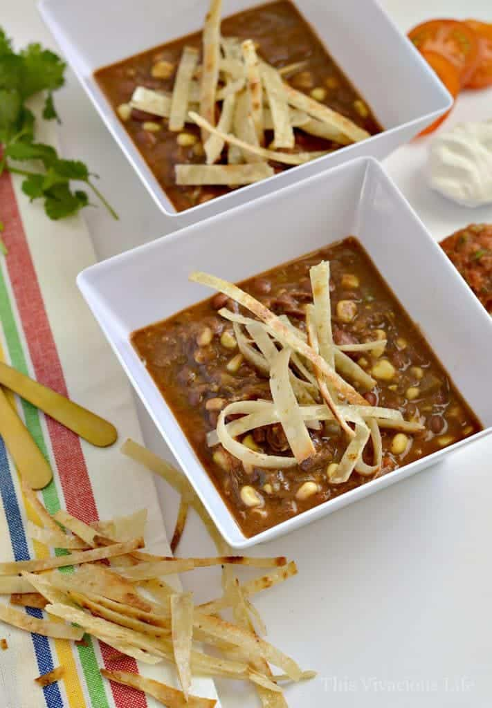 Shredded beef crockpot taco soup with tortilla strips in a bowl
