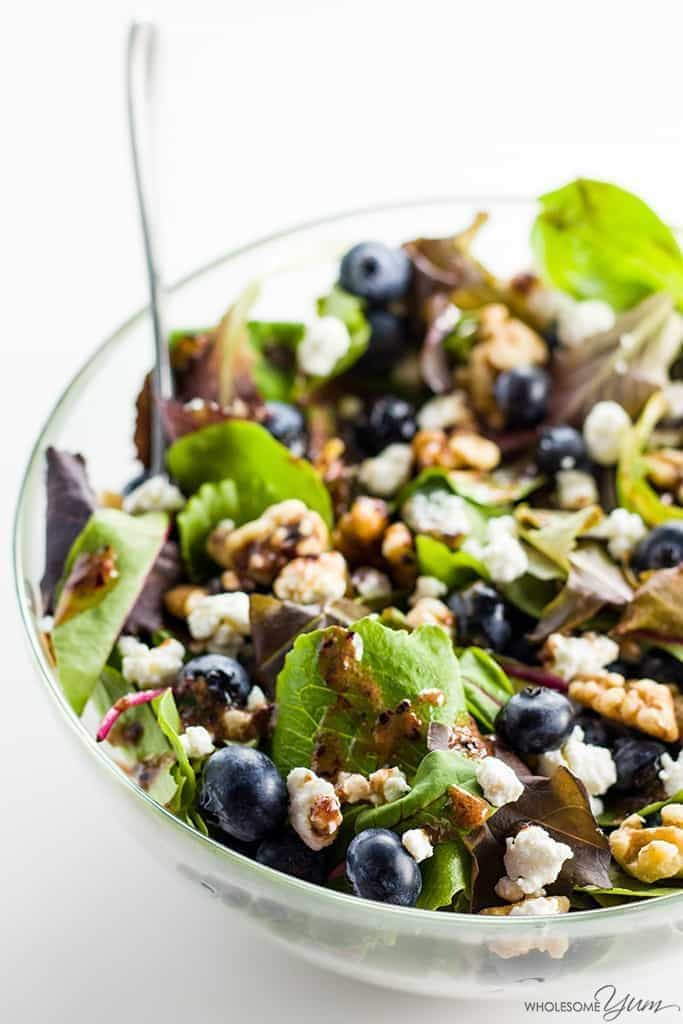 Berry and nut green salad in a clear bowl