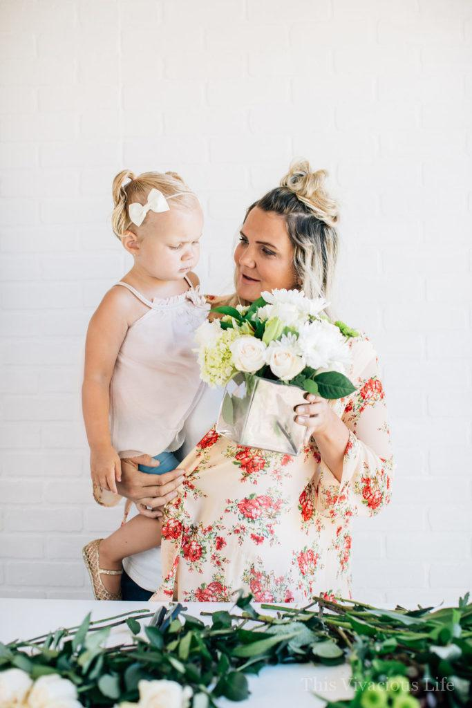 Mom and little girl with modern white flower arrangement