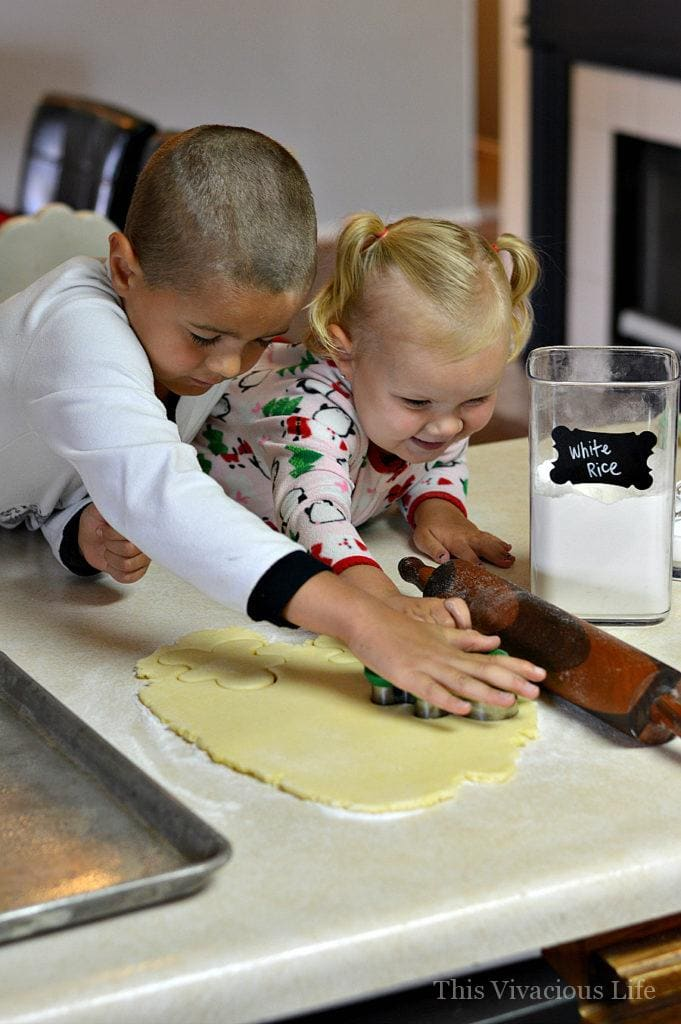 Kids making sugar cookies with dough and rolling pin