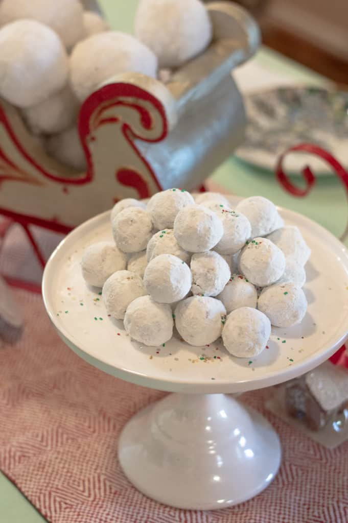Powdered donut holes on a white cake stand
