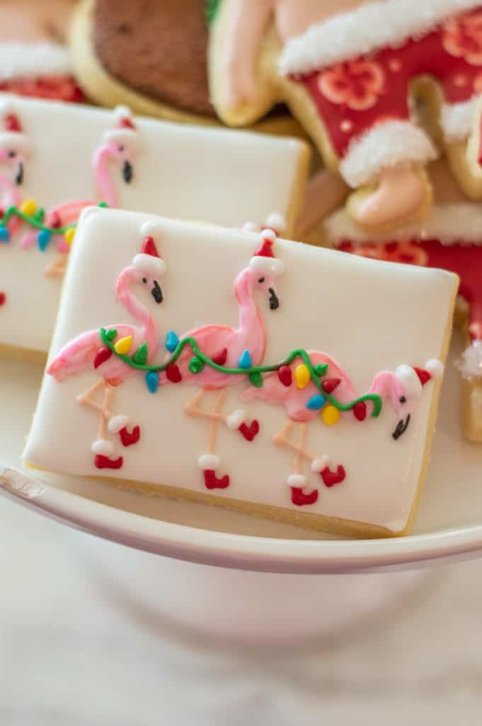 White frosted sugar cookie with Christmas flamingos