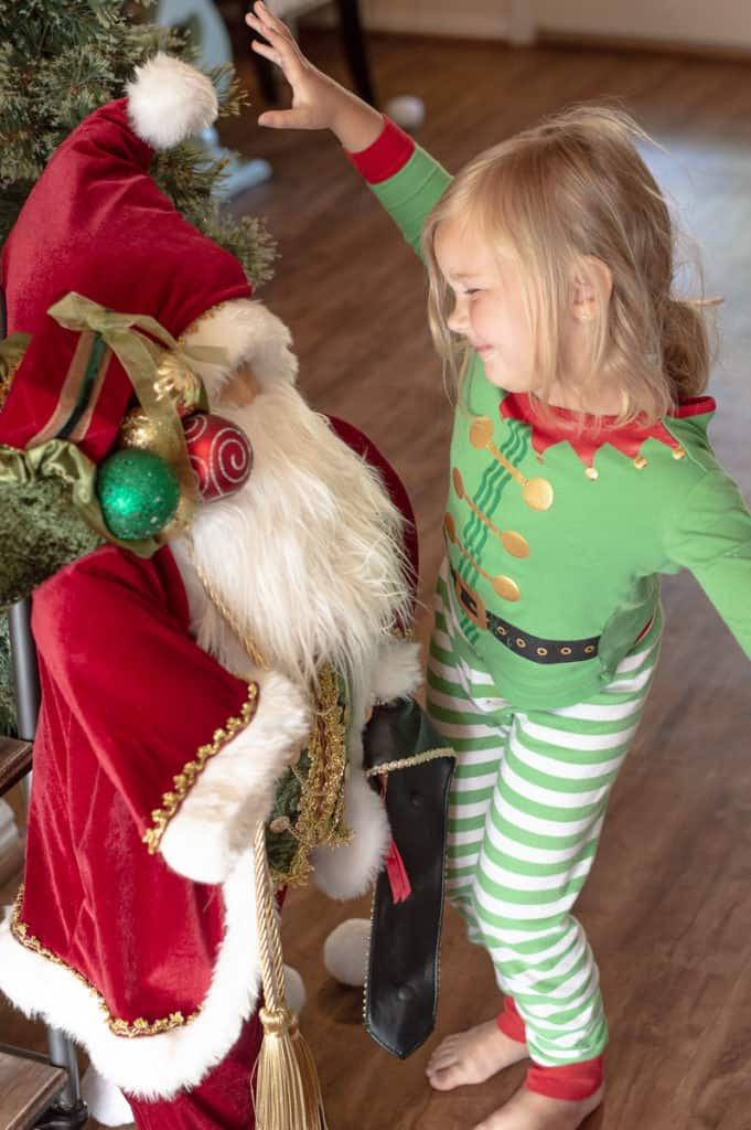 Santa decoration with little girl in Christmas pajamas