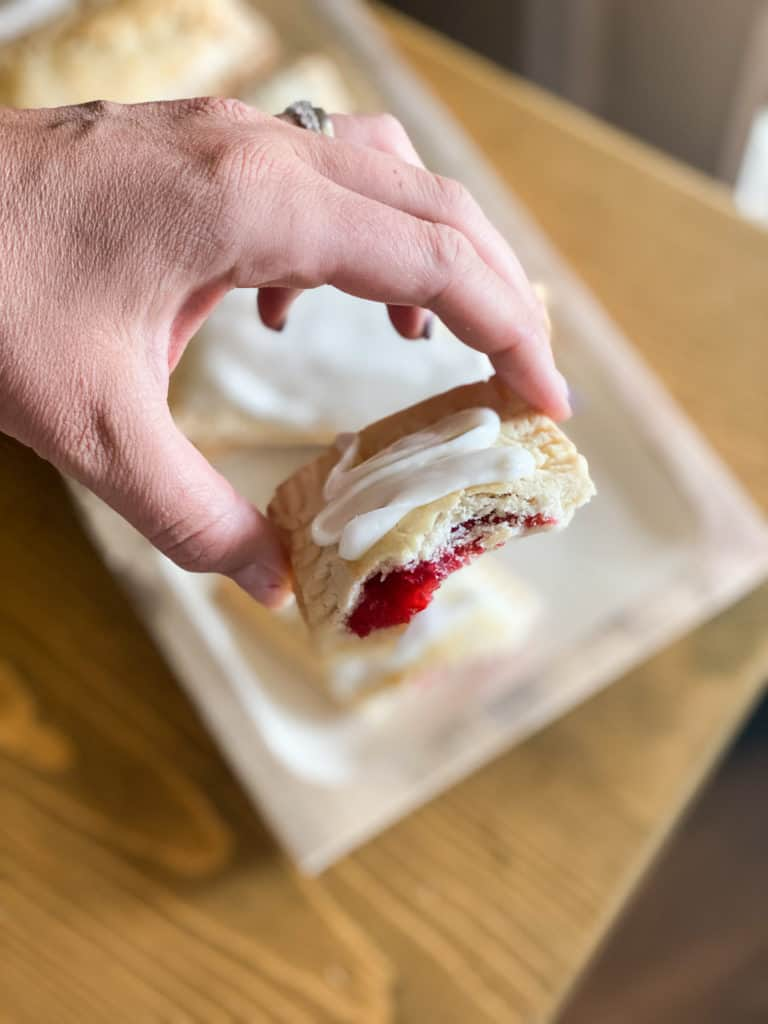 Gluten-Free Pop Tarts in a hand with raspberry filling