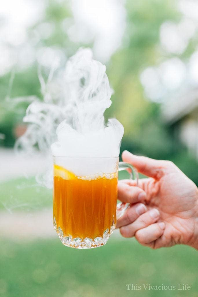 Smoking Halloween pumpkin punch in a glass cup