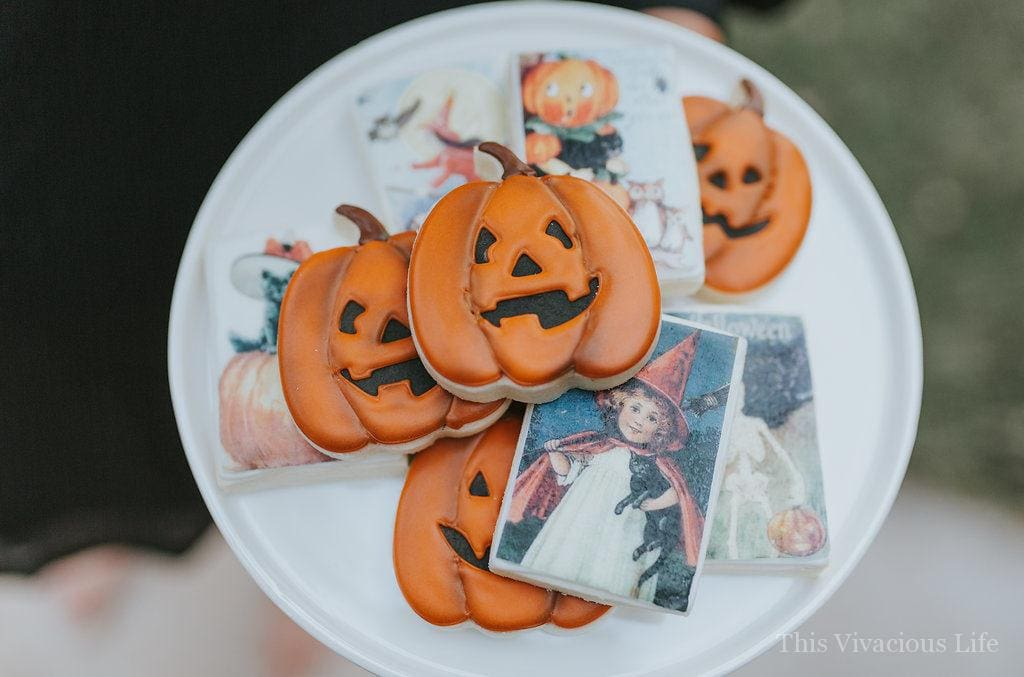 Halloween jack o' lantern and witch cookies on a white plate