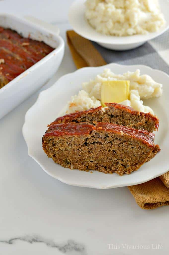 Two slices of meatloaf with ketchup on a white plate