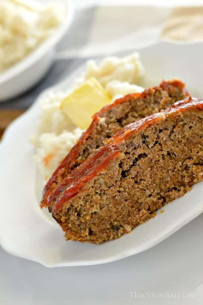 Two slices of meatloaf on a white plate with mashed potatoes