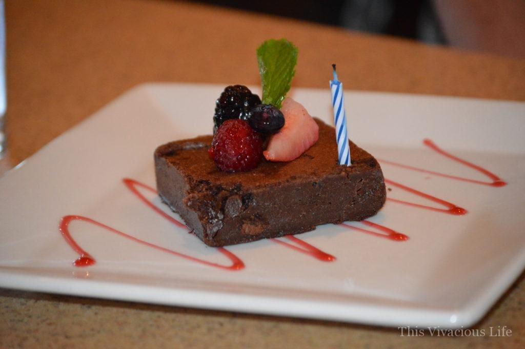 Gluten-free brownie with fruit on a white plate