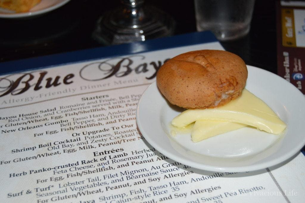 Blue Bayou menu with a gluten-free roll and butter on a white plate
