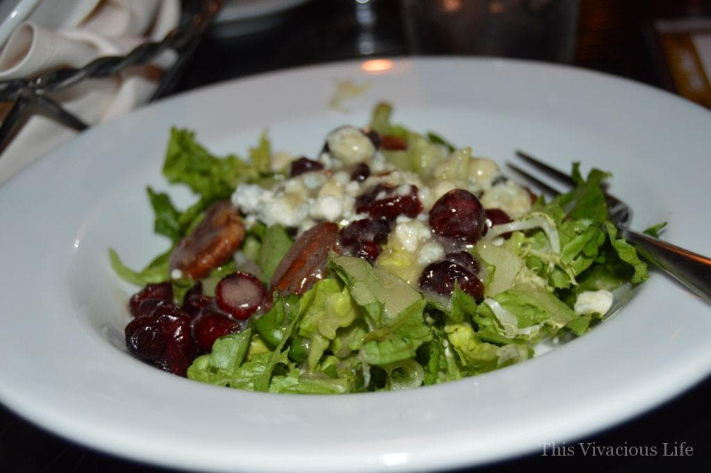 Green salad with pecans and cranberries in a white bowl
