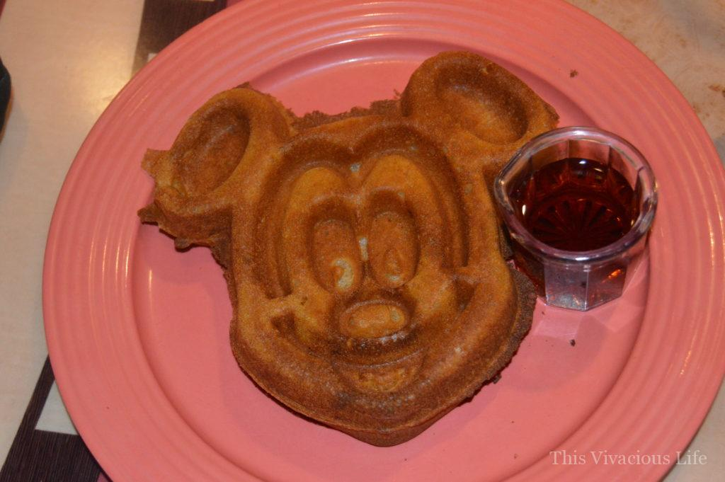 Gluten-free Mickey Mouse waffle and syrup on a coral plate