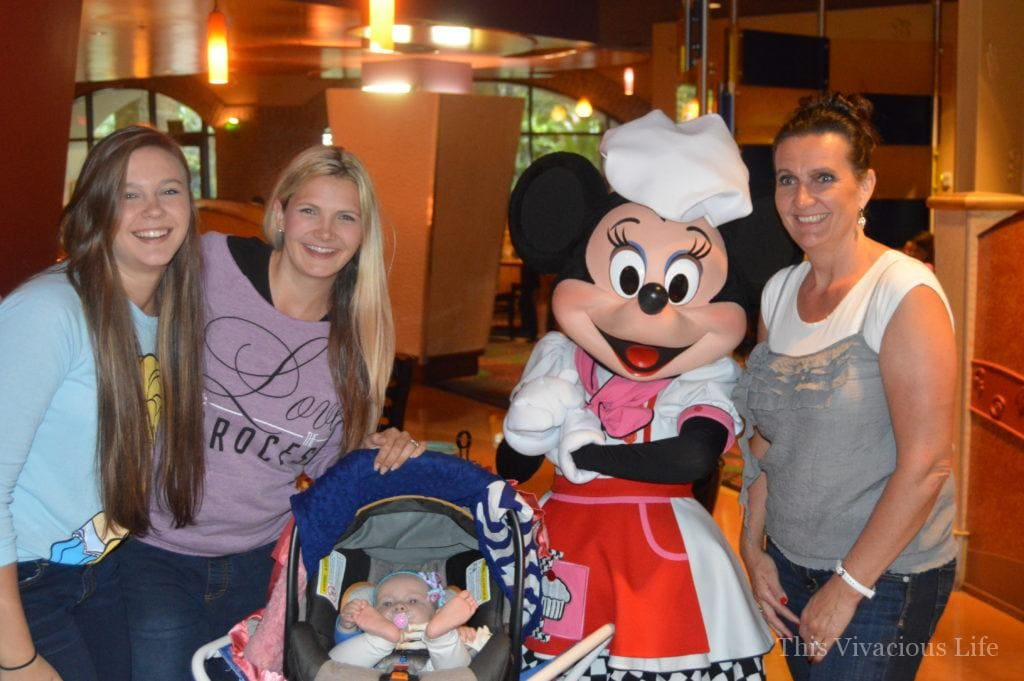 Three women and a baby meeting Minnie Mouse