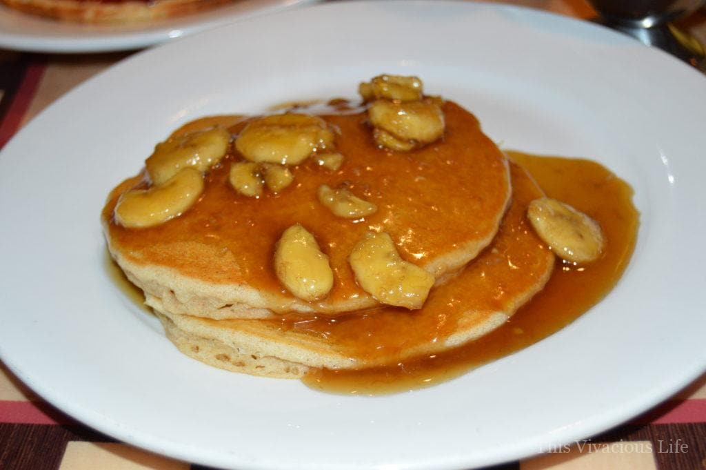 Two gluten-free pancakes with bananas foster on a white plate