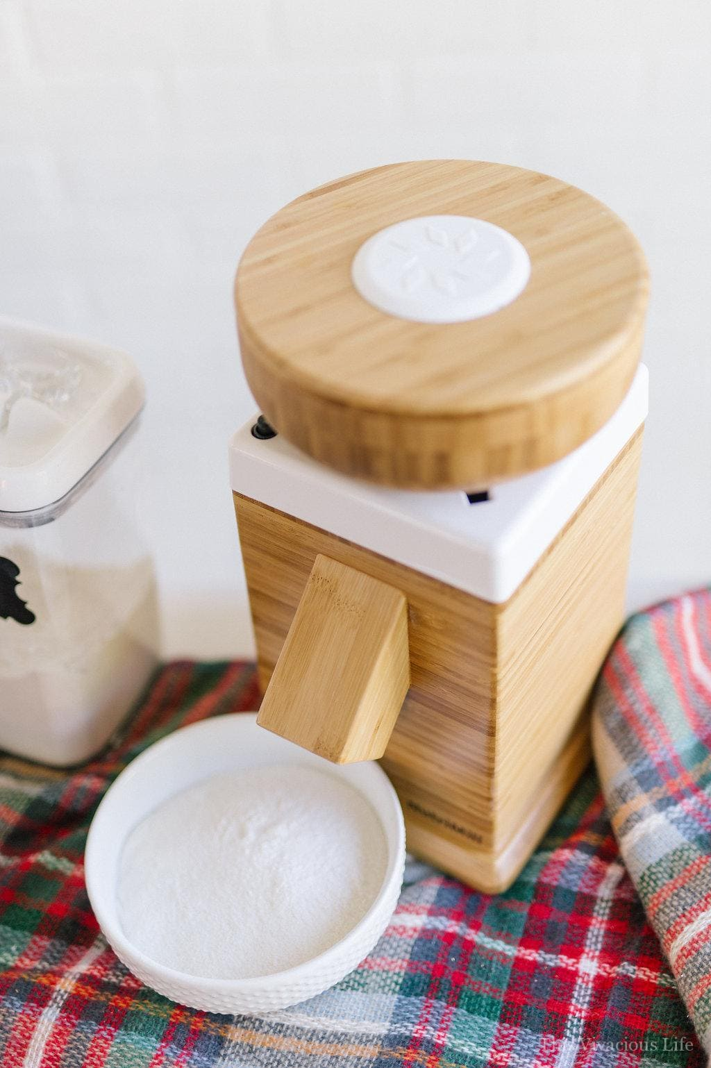 Wood Nutrimill flour grinder on a plaid blanket