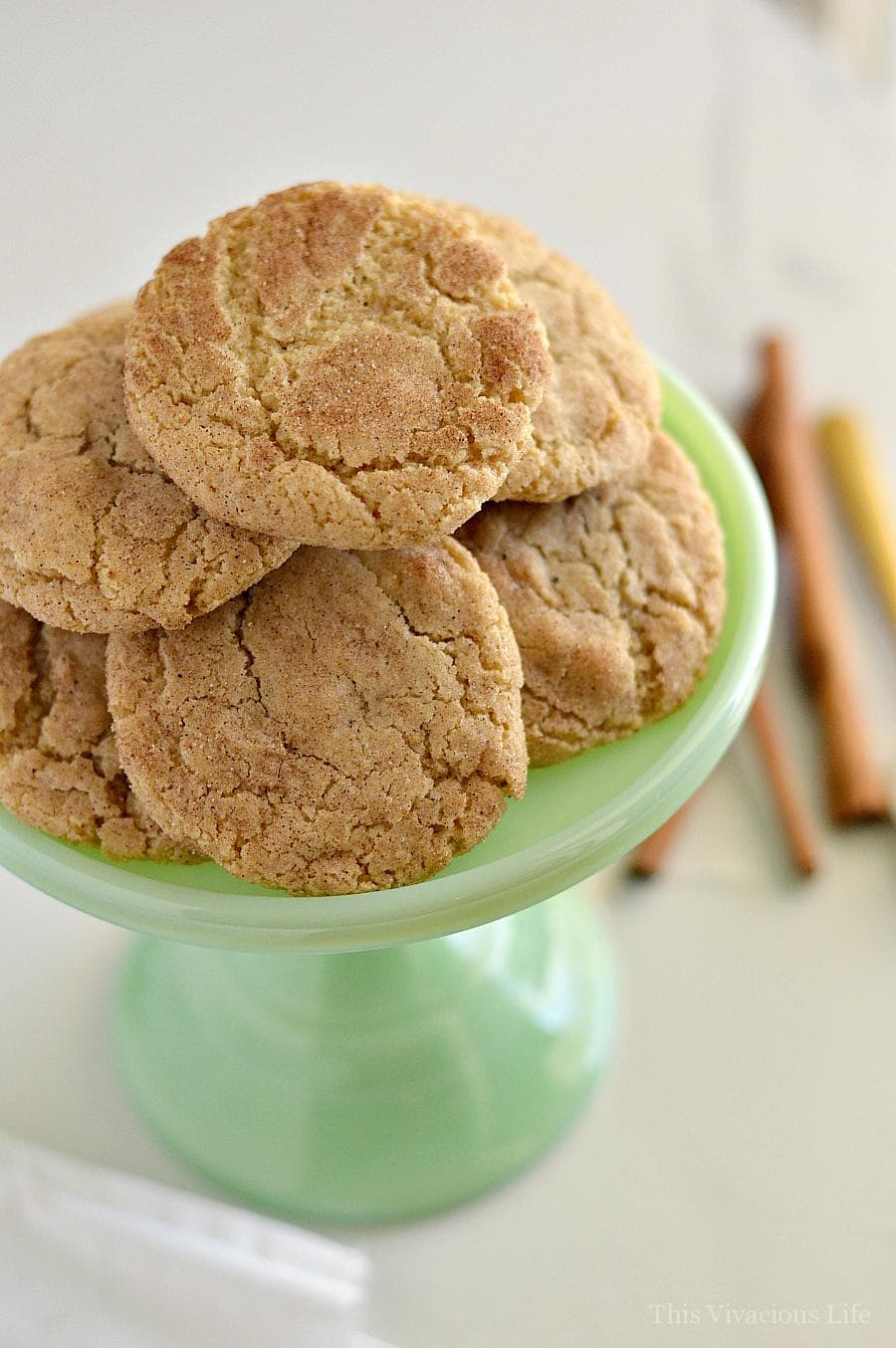 Snickerdoodles in a pile on a small jadeite cake stand
