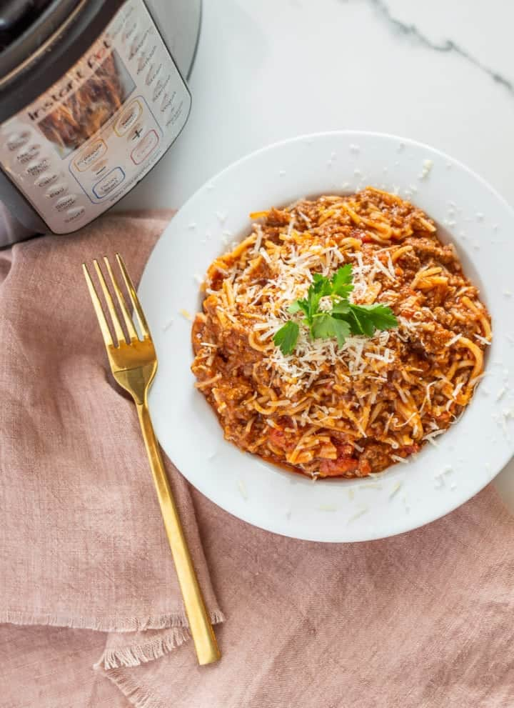 Spaghetti in a white bowl next to an Instant Pot