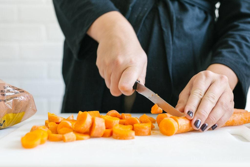 Carrots being chopped with a knife