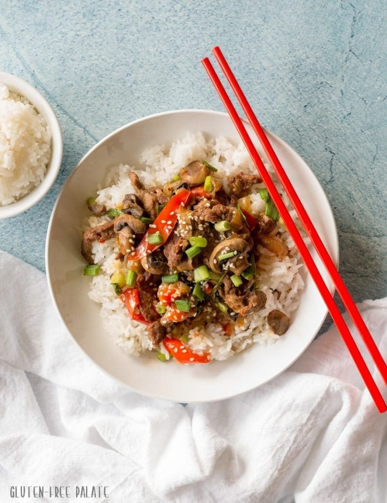 White bowl with rice and beef and red chopsticks