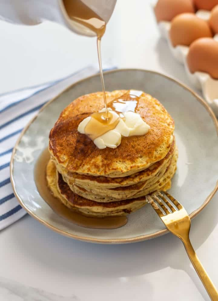 Shortstack of pancakes with syrup being drizzled on top