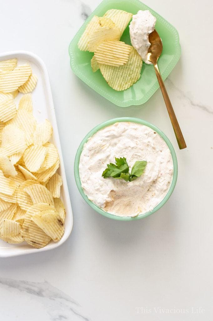 An overhead view of Sour Cream Dip with Cream Cheese & Cheddar next to a Ridged Chips