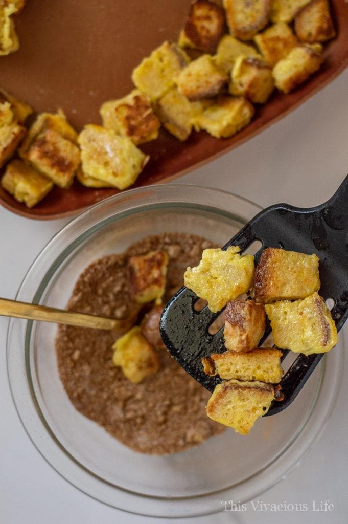 French toast bites in a frying pan and on a spatula