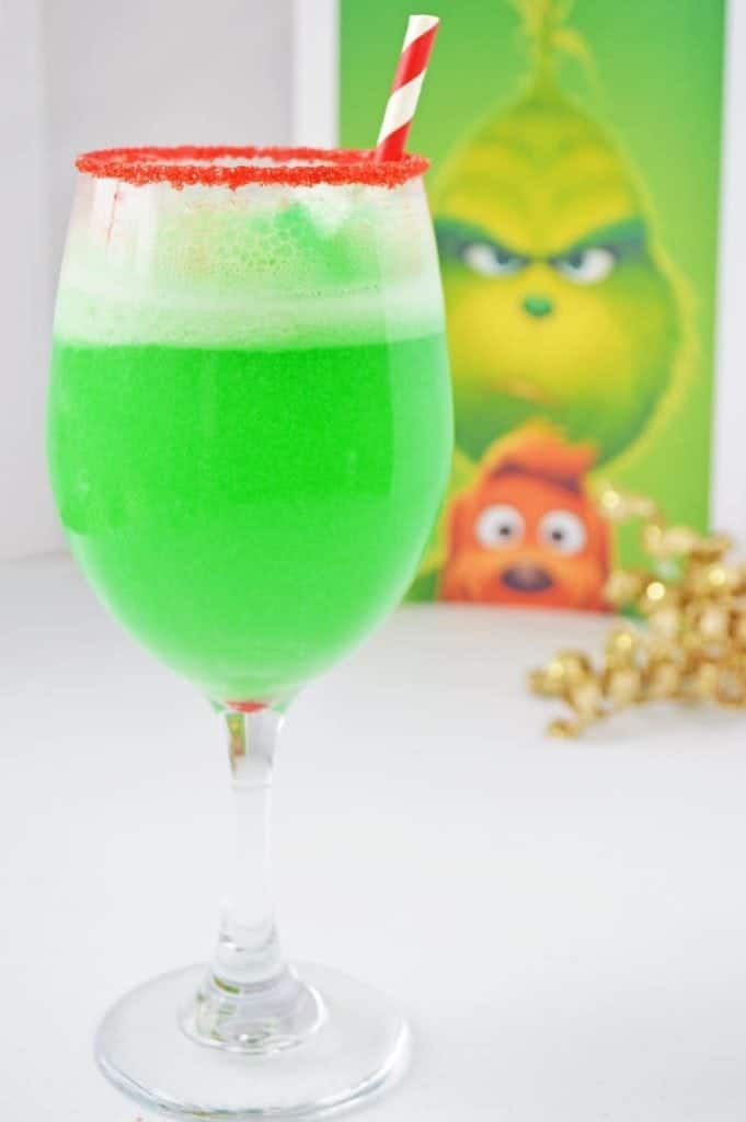 Green Grinch punch in a glass cup with red sugar rim