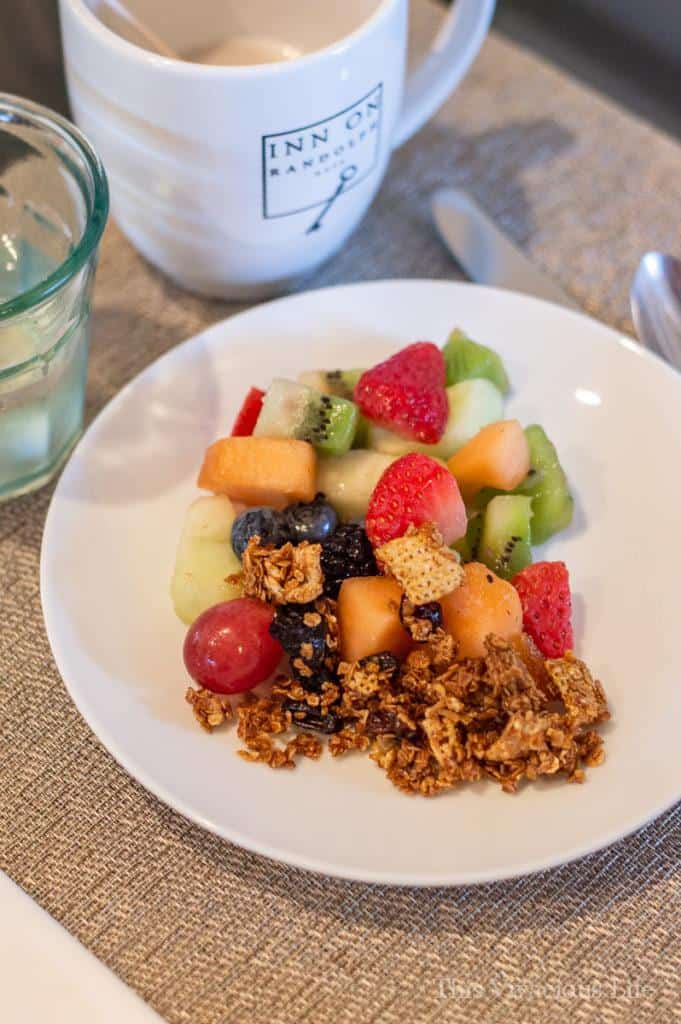 Fresh fruit with granola on a white plate