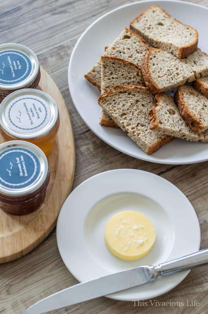 Three jam jars, sliced gluten-free bread and butter