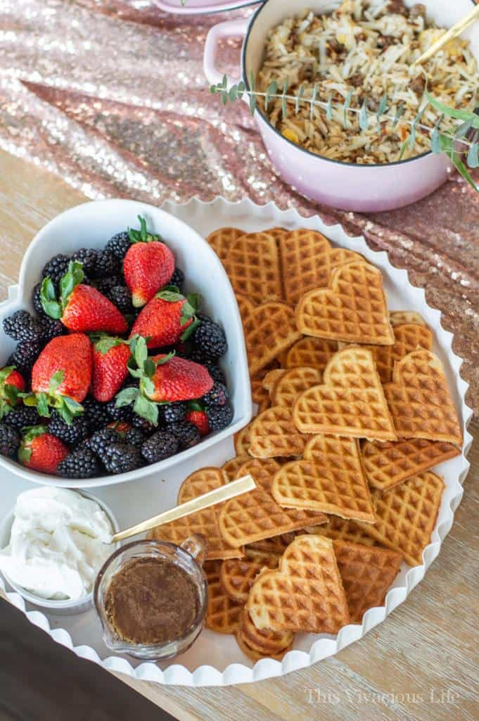 Heart waffles and berries on a white tray