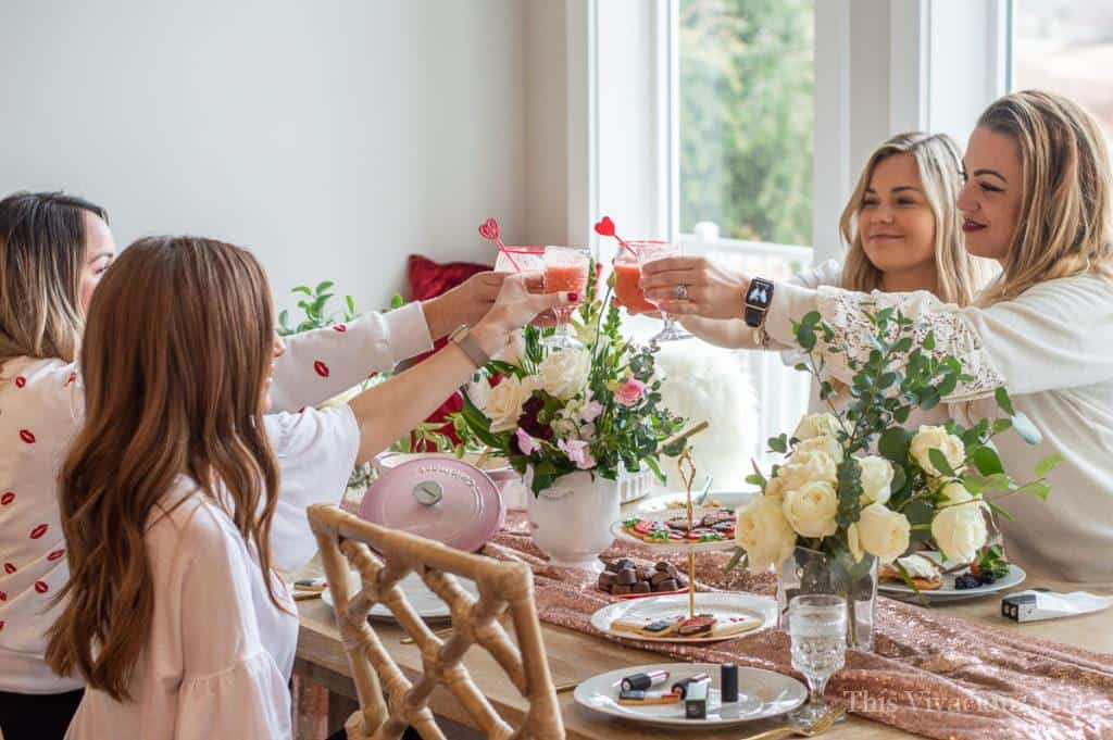 Four girls doing a cheers at a table with flowers