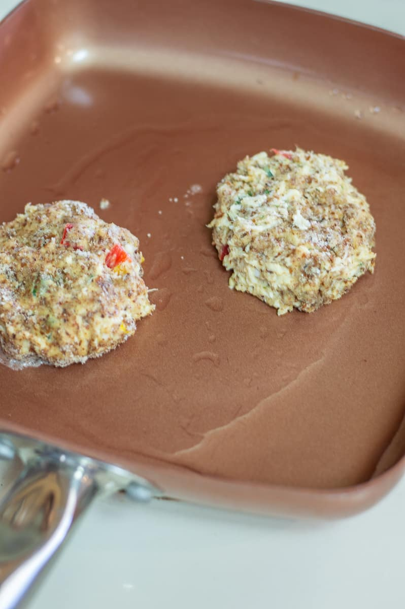 Two crab cakes frying in a copper pan